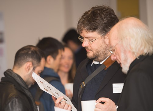 Photo of delegates looking at programme document at Urban Big Data Centre event